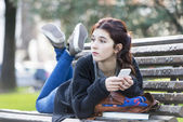 Pensive girl lying on bench with phone, adolescense lifestyle. — Stock Photo
