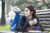 Pensive beautiful girl lying on bench, adolescence lifestyle. — Stock Photo
