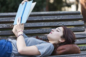 Beautiful girl lying on bench reading blue book, outdoor. — Stock Photo