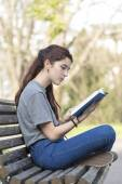 Beautiful caucasian girl sitting on bench, reading blue book. — Stock Photo