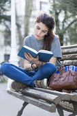 Young beautiful woman reading blue book in the street. — Stock Photo