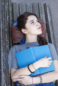 Pensive girl lying on bench with book, adolescence lifestyle. — Stock Photo