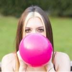Closeup portrait of beautiful girl inflating balloon, outdoor. — Stock Photo #75244201