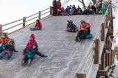 Funny people slide down the ice slide — Foto de Stock