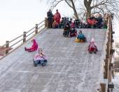 Funny people slide down the ice slide — Stock Photo