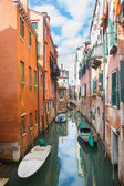 Gondolas parked next to buildings in water canal — Stock Photo