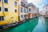 Gondolas parked next to houses in water canal — Stockfoto