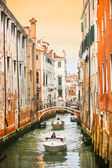 Boats sailing in water canal with orange buildings — Stock Photo