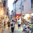 Постер, плакат: Tourists walking next to displayed souvenirs in Rovinj