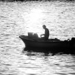 Man in motor boat at sunset bw — Stock Photo #78469740