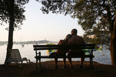 Couple sitting on bench at sunset — Stock Photo