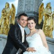 Bride and groom posing in front of fountain — Stock Photo #81159220
