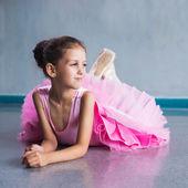 Молодая балерина в розовой одежде сидит на полу во время обучения в танцевальный класс. — Стоковое фото