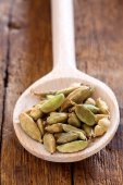 Wooden spoon with green cardamom pods — Stock Photo