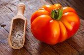 Ripe beefsteak tomato and salt in spice scoop — Zdjęcie stockowe