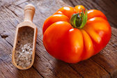 Ripe beefsteak tomato and salt in spice scoop — Stockfoto