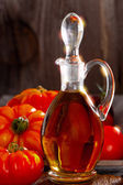 Fresh meat tomatoes and a carafe of olive oil — Stock Photo
