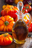 Carafe of olive oil and ripe beef tomatoes — Stock Photo