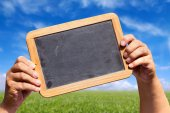 Hands holds a slate blackboard with advertising space — Stock Photo