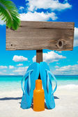 Wooden signboard under palm frond — Stock Photo