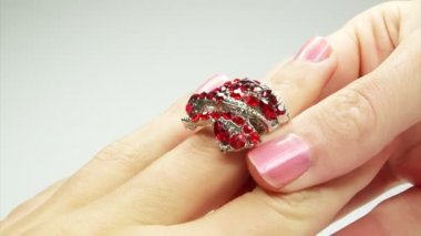 Jewelery ring with red ruby crystals putting on the finger — Stock Video