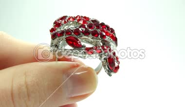 Jewellery ring with red ruby crystals putting on the finger — Stock Video