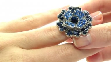 Jewelery ring with blue sapphire crystals putting on the finger — Stock Video