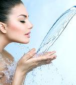 Girl under splash of water — Stock Photo