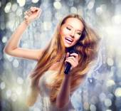 Girl with a microphone singing — Stock Photo