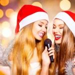 Girls in santa hats singing — Stock Photo #60807763