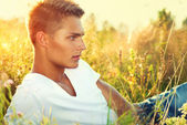 Handsome guy lying on the field. — Stock Photo