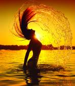 Girl splashing water with hair — Stock fotografie
