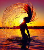 Girl splashing water with her hair — Stock fotografie