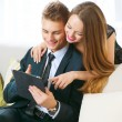 Young couple with tablet pc chatting or buying online — Stok fotoğraf #74136773
