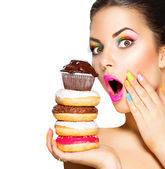Girl taking sweets and colorful donuts — Stock Photo