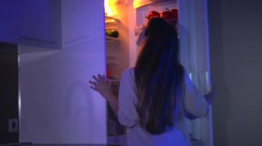 Girl gets  cake from  fridge at night — Stock Video