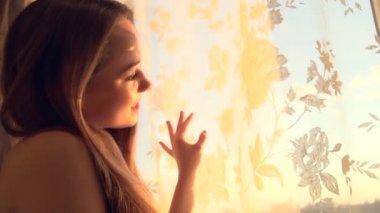 Girl opens curtains on big window — ストックビデオ