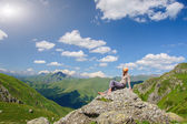 A woman sits on the edge of the cliff and looking at the sun valley and mountains — Stock Photo