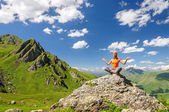 Young woman sitting in yoga pose in mountains — Stock Photo