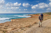 Hiker with backpack walking on seaside. — Stock Photo