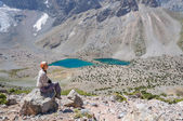 Woman sitting near lake in the mountains — Stock Photo