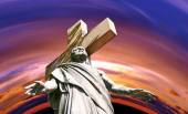 Crucified Jesus Christ against dramatic sunset — Stockfoto