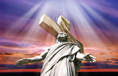 Dramatic sunset with statue of crucified Jesus Christ — Стоковое фото