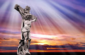 Dramatic sunset with statue of crucified Jesus Christ — Photo