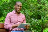 Happy guy using his tablet pc, outdoors — Stock Photo