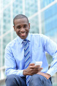 Business executive using his smart phone — Stock Photo