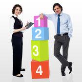 Gente de negocios al lado de bloques números — Foto de Stock