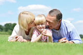 Parents lying and kissing their daughter — Stock Photo