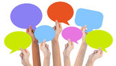 Hands holding colorful speech bubbles — Stock Photo