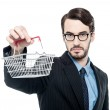 Businessman showing small shopping cart — Stock Photo #64734599